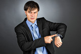 Young businessman pointing to his watch with an angry expression