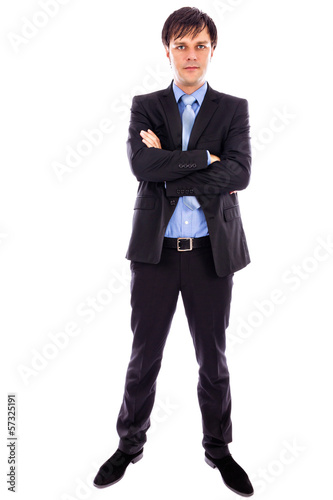 Full length portrait of a young businessman standing with arms f