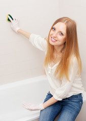 long-haired woman cleaning tile  in bathroom