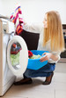 blonde woman loading the washing machine