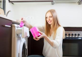 woman putting whitener in to washing machine