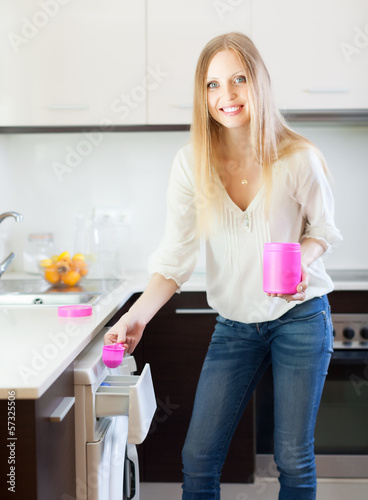 woman putting whitener in to washing machine