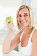 Young smiling woman holding a green apple looks into the camera