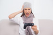 Furious brunette with winter hat on playing video games