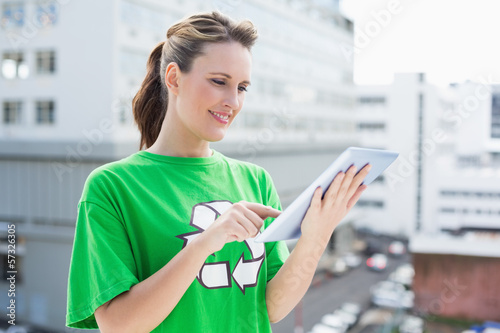 Smiling woman wearing recycling tshirt using tablet