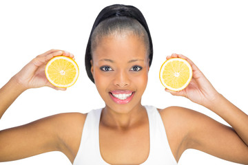 Smiling woman holding slices of orange