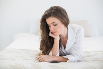 Thoughtful casual brown haired woman in white pajamas lying on h