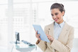 Pleased smart brown haired businesswoman using a tablet pc