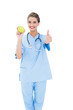 Cheering brown haired nurse in blue scrubs holding a green apple