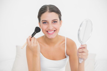Happy young brown haired model in white pajamas applying powder