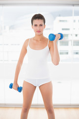 Serious natural brown haired woman in white sportswear exercisin