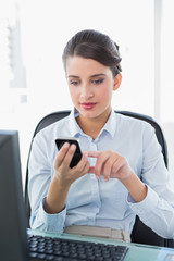 Concentrated classy brown haired businesswoman texting with her
