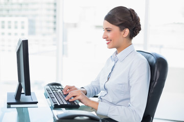 Cheerful classy brown haired businesswoman using a computer