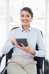Joyful classy brown haired businesswoman using a calculator