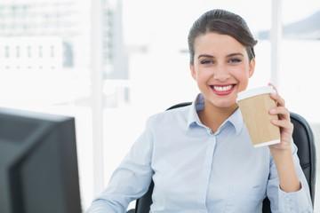 Beautiful classy brown haired businesswoman enjoying coffee