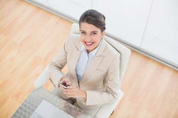 Delighted smart brown haired businesswoman using a mobile phone