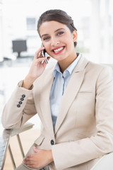 Cheerful smart brown haired businesswoman making a phone call