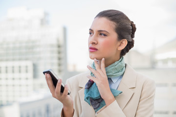 Thoughtful smart brown haired businesswoman holding a mobile pho