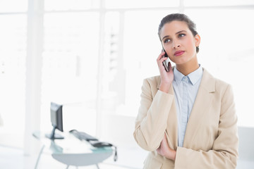 Serious smart brown haired businesswoman making a phone call