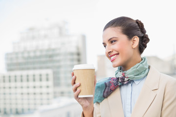 Happy smart brown haired businesswoman holding a cup of coffee