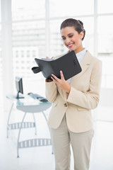 Content smart brown haired businesswoman filling an agenda