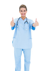 Joyful brown haired nurse in blue scrubs giving thumbs up