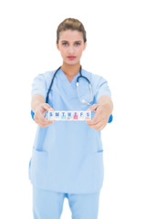 Serious brown haired nurse in blue scrubs showing a medication b