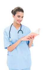 Joyful brown haired nurse in blue scrubs holding a book