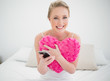 Natural cheerful blonde holding heart pillow and smartphone