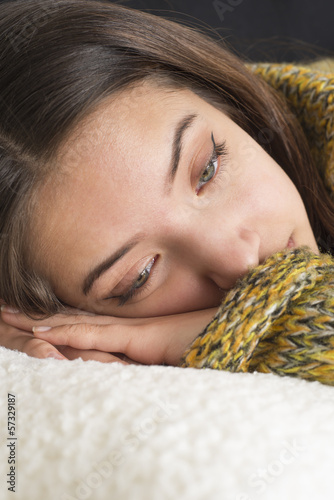 Pensive young woman lying on couch