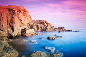 Sunset panorama over sea and rocks; long exposure