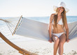 Pretty blonde wearing bikini and sunhat sitting on hammock and s