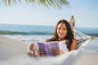 Peaceful woman lying on hammock reading book