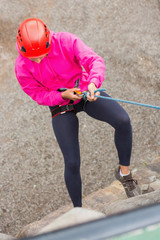 Fit girl abseiling down rock face