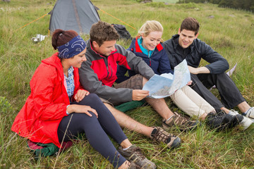 Friends sitting down looking at map on camping trip
