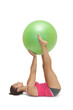 Calm sporty brunette lying on floor holding exercise ball betwee