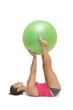 Calm sporty brunette lying on floor holding exercise ball betwee