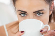Close up of a cute brunette woman drinking coffee