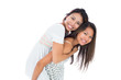 Smiling asian woman giving her sister a piggyback ride