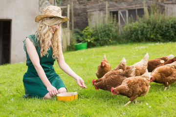 Young pretty blonde feeding her chickens