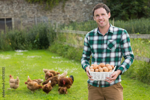 Proud young man holding a basket filled with eggs