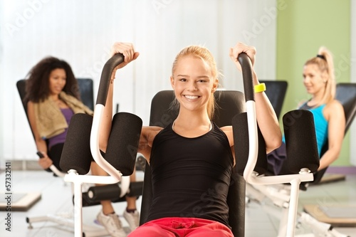 Young girl exercising at gym smiling