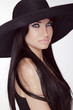 Fashion brunette woman model posing in black hat isolated on whi