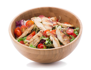 Grilled chicken salad in wooden bowl isolated on white