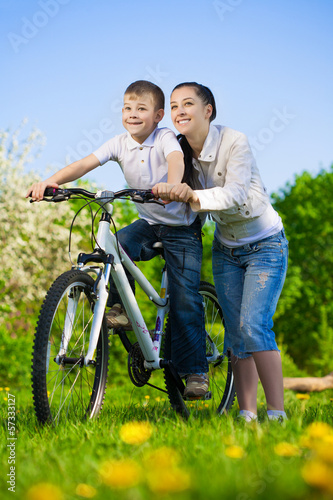 family in a green park with a bike