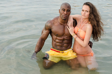 Fit couple relaxing at the beach