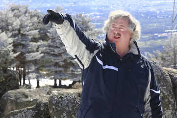 mature man with silver hair pointing his arm a place in the snow