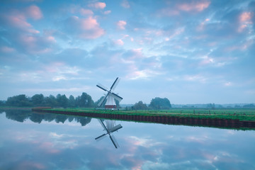 charming Dutch windmill by river during sunrise