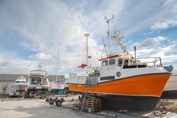 Small fishing boats lay on the coast in Norwegian wharf