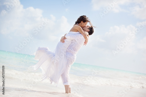 bride and groom kissing on a tropical beach